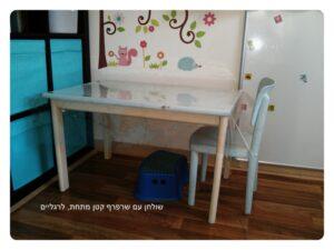 שולחן מעץ עם שרפרף תחתיו להנחת הרגליים