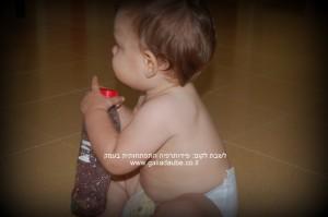 תינוקת יושבת בגיל שמונה חודשים